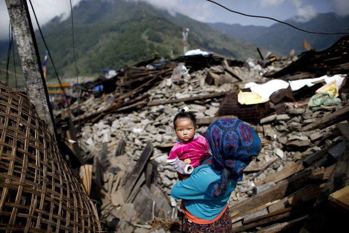 epaselect epa04729942 A picture made available 02 May shows a woman carrying her baby through what is left of Barpak village, epicenter of the devastating earthquake that hit the country on 25 April 2015, Nepal, 01 May 2015. The confirmed official death toll increased to 6,621, with more than 14,000 injured, an Interior Ministry spokesman said. The 7.8-magnitude earthquake was the deadliest in the country for more than 80 years, destroying an estimated 300,000 houses across northern Nepal.  EPA/DIEGO AZUBEL